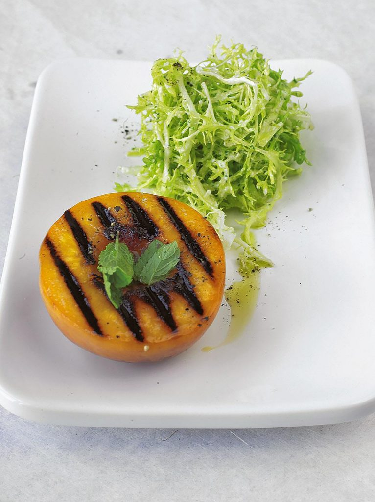 Warm grilled peach and frisée salad with goats cheese dressing
