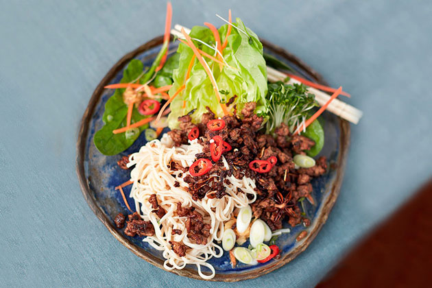 asian spicy beef noodle dish with salad and chilli