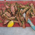 Healthy steak cooked medium rare and sliced on a board with lemon
