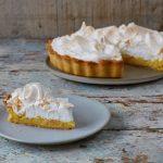 lemon meringue pie with a slice cut out of it