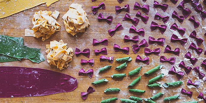 different shapes and colours of pasta on a board