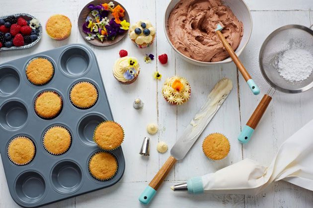 vanilla cupcakes and baking equipment with icing bag and tray
