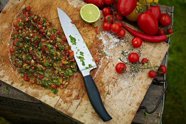kitchen chopping board with fresh herbs and tomatoes and chilli