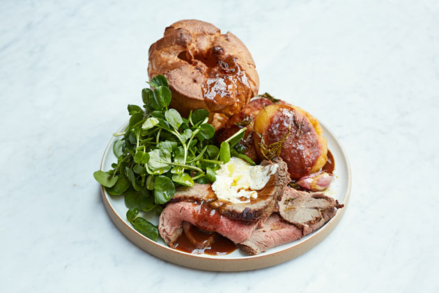 Plate of Yorkshire puddings, slices of roast beef and salad