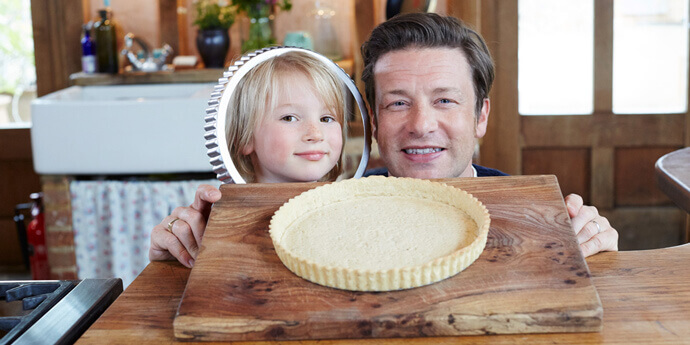 jamie and his son with a freshly baked pastry dish on a wooden board
