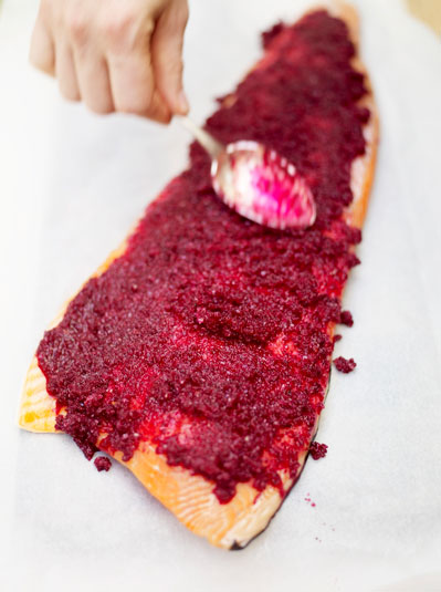 blended berries being spread on the salmon