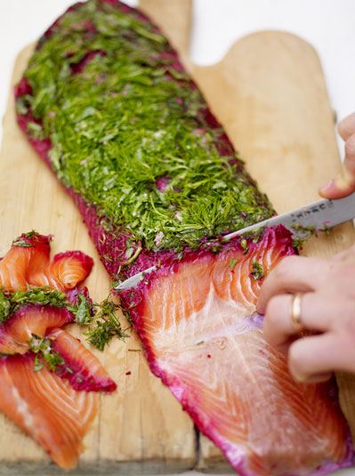 salmon being sliced with herbs on top
