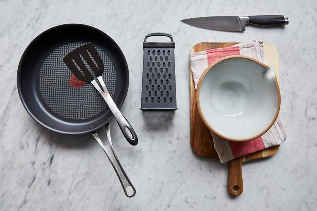 Matériel pour faire des pommes de terre rissolées: poêle, spatule, râpe, couteau, bol, hachage planche et torchon