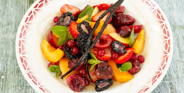 chopped fruit in a bowl with a vanilla stick in and syrup