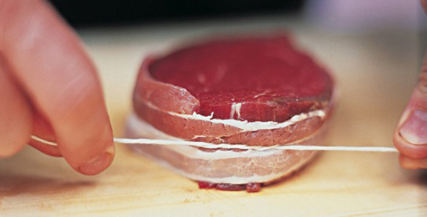 raw meat being tied up with string by butcher