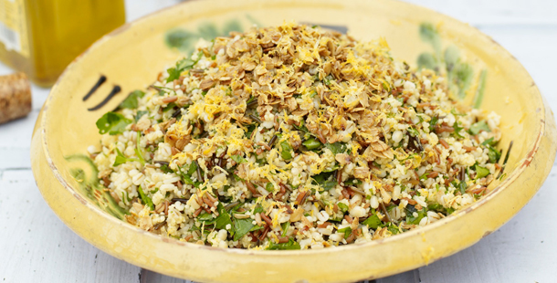 a bowl full of grains with chopped herbs and salad leaves