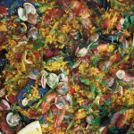 paella in a metal dish with lemon slices and mixed seafood