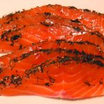 sliced raw salmon with seaweed and seeds on top