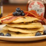 stack of blueberry pancakes with syrup and bacon on top