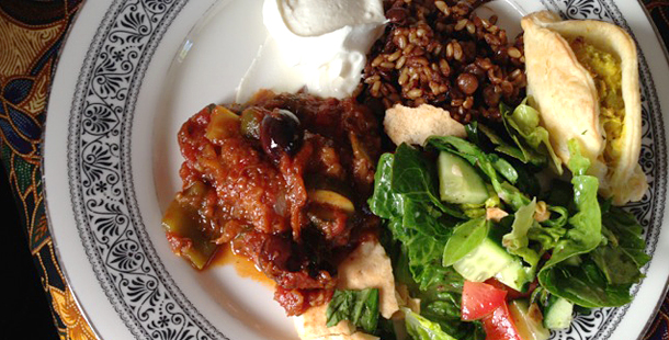 vegetarian dish with olives, salad, rice and sour cream on the side