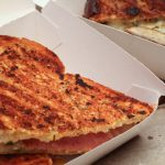 cheese and ham toasted sandwich in cardboard box