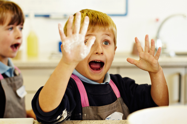 kid with flour on hand