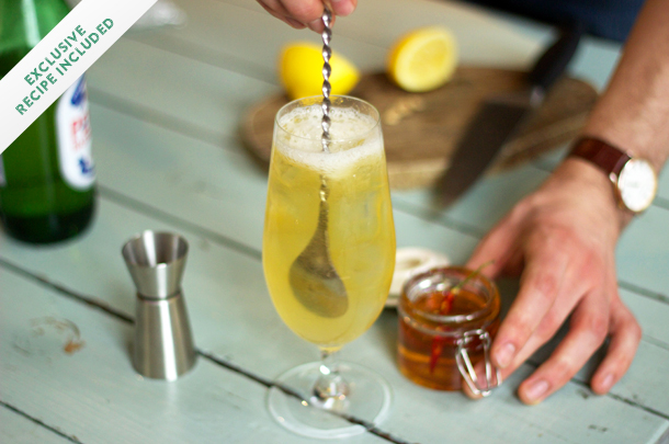 cocktail recipe being stirred with honey on the side