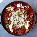 veggie chilli with sour cream and rice on top
