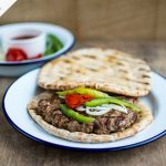 Bosnian burger meat on a flatbread with onions and chilli on top