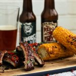bbq corn on the cob with ribs covered in chilli next to beer