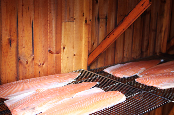 smoked salmon slices on a grill in wooden shed