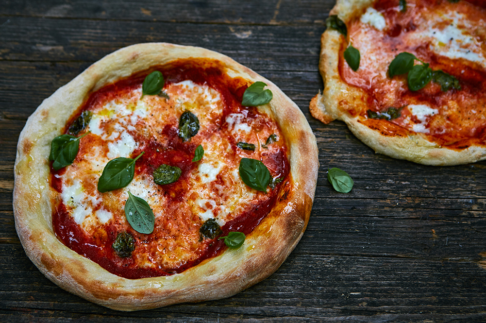 how to make pizza - 2 pizzas with basil, mozarella and tomato on top