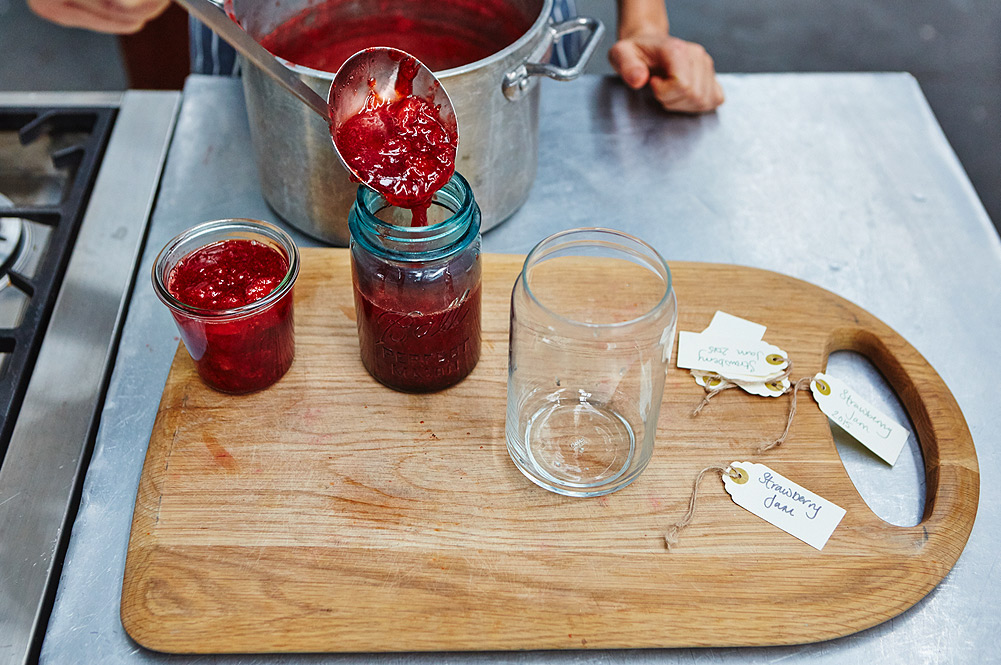 make jam - being spooned into mason jars