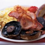 full english breakfast on a plate with scrambled eggs