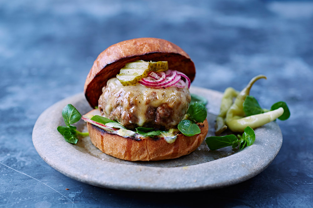 goat meat burger with lettuce, onions and gherkin