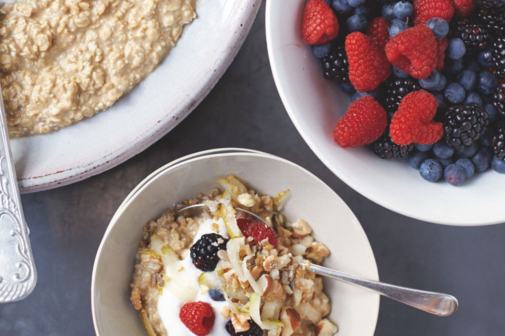 Healthy breakfast with bowls of granola, porridge and fruit