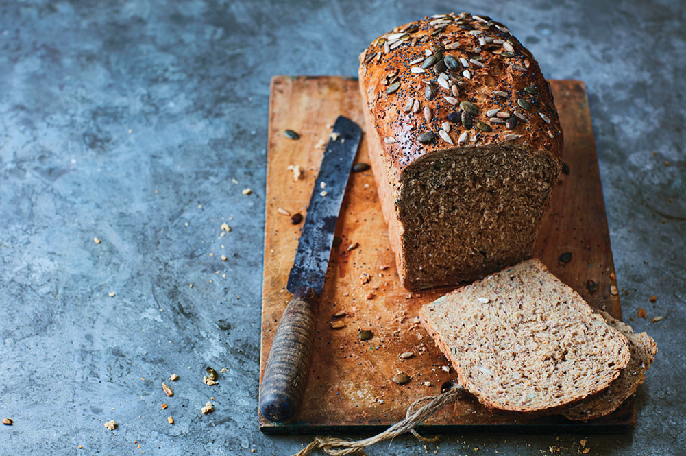 granary bread with seeds on top being sliced on a bread board