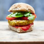 vegan burger with ketchup, tomatoes and coriander in a burger