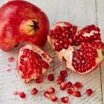 pomegranate cut open with seeds out of it