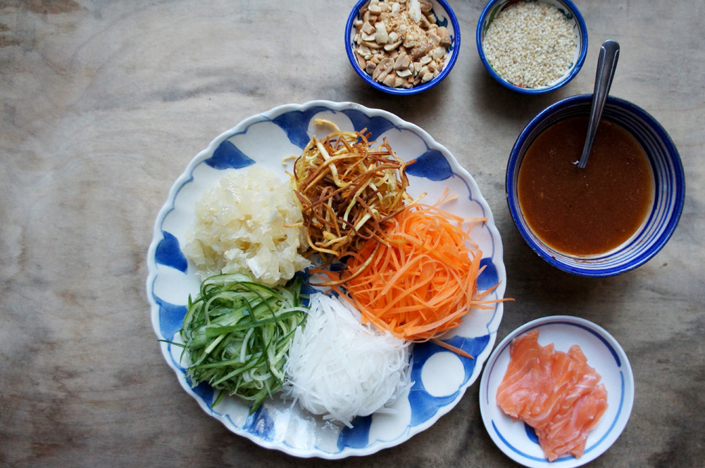 bowl of yu sheng, shredded vegetables with salmon and sauces next to it