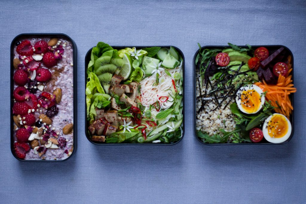 bento boxes with Asian inspired recipes. Fruit fishes and vegetable salad dishes.