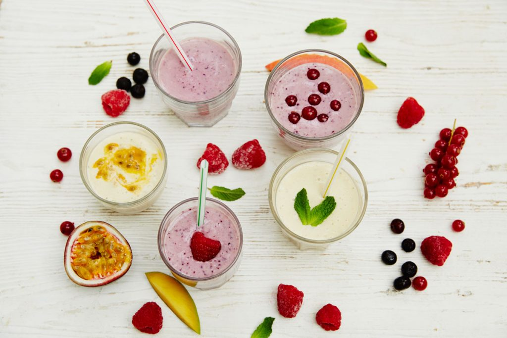 smoothies flat lay with fruit scattered around the glasses