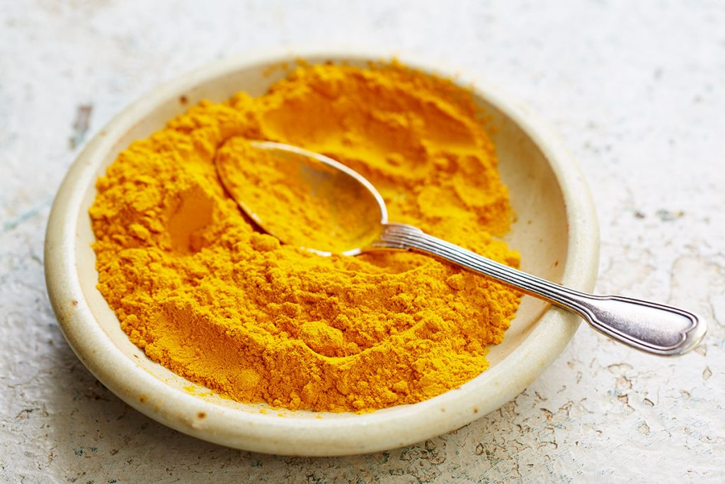 a plate of turmeric with a spoon dipped in it