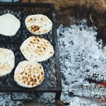 middle eastern pitta bread being cooked on a bbq