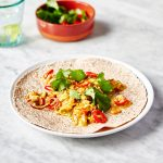 masala scrambled egg with chilli and coriander on top, on top of a wrap