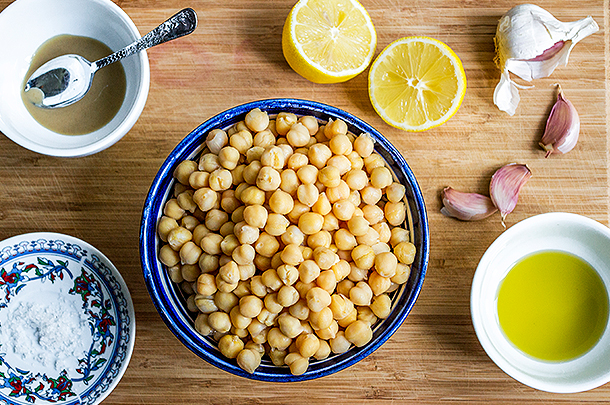 Image of ingredients for humous including a bowl of chickpeas, some lemons, garlic and tahini