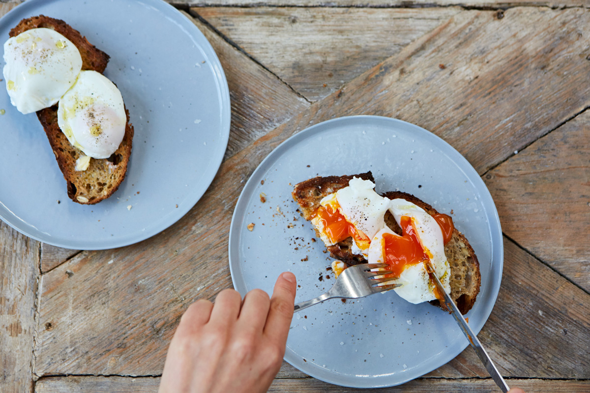 Image of poached egg on toast being cut open with a knife and fork