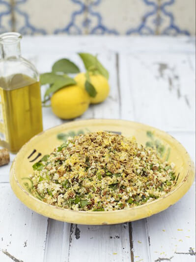 yellow plate with a grain salad, lemons and olive oil