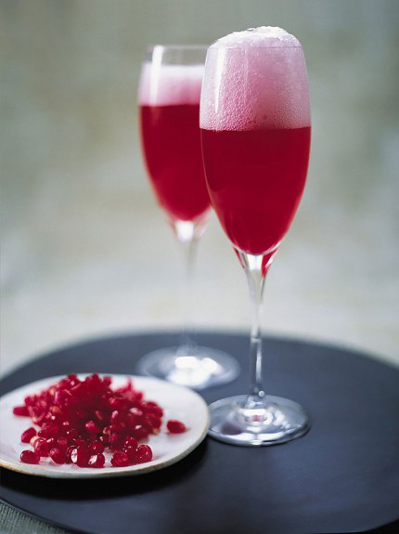 two glasses of champage and pomegranate juice and a plate of pomegranate seeds