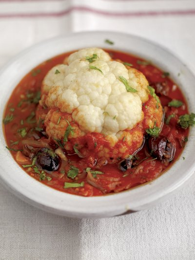 Whole baked cauliflower with tomato and olive sauce